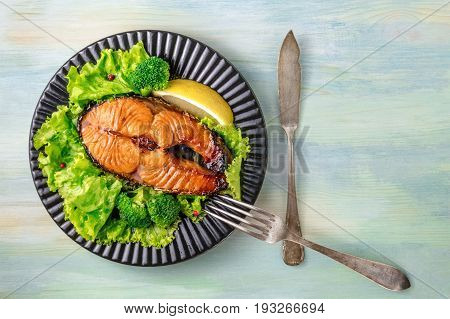 An overhead photo of a grilled salmon steak, with fresh green salad, broccoli sprouts, a slice of lemon, and pink peppercorns, with a fork and a knife, on a teal background with a place for text