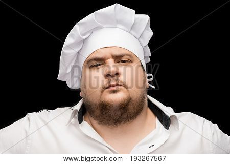 dissatisfied young chef in white hat looking at camera isolated on black