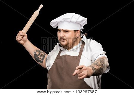 Serious Professional Chef Holding Rolling Pin And Pointing At Camera
