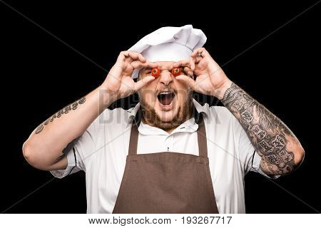Professional Chef In Hat And Apron Holding Cherry Tomatoes And Grimacing