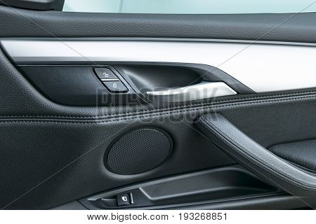 Car door handle inside the luxury modern car with black leather and switch button control modern car interior details