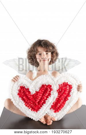 Young Pretty Kinky Angel With Two Hearts Sitting On The Floor With Cute Smile, Looking Into The Came
