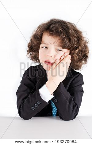 Little curly manager in a business suit sitting crying and holding both hands on the cheek. White background.