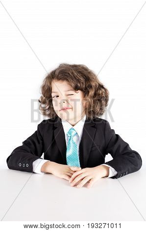 Young Curly Manager Sits At A Table, Winked At The Camera. White Background.
