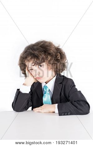 Little Curly Manager In A Business Suit Sits Propped On His Head Hand Covering Eyes Thoughtful Looki