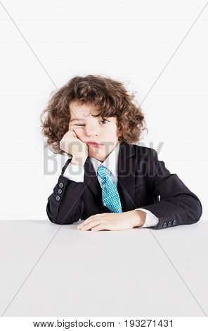 Little Curly Manager In A Business Suit Sits Propped On His Head Hand Covering Eyes Sad Looking At T