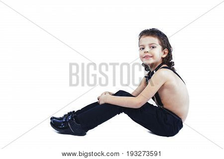 A Cute Boy In Suspenders Sits And Looks Into The Camera. Close-up. White Background.