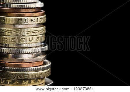 Stack of British coins over black.  Finance background with copy space.