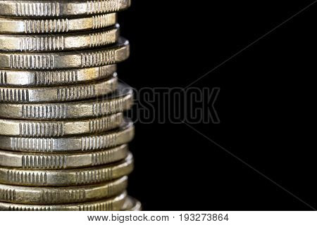 Stack of coins over black.  Finance background with copy space.