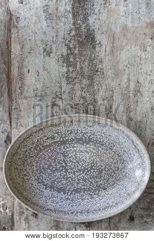 Empty oval dish on rustic timber.  Top view.  Food background.