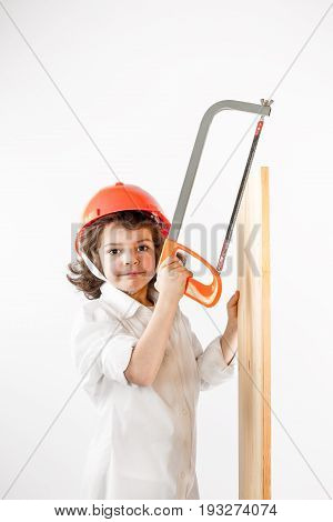 Little cute worker works with a hacksaw and board. Gray background.