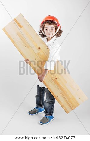 Young curly worker in a helmet holding board. Gray background.