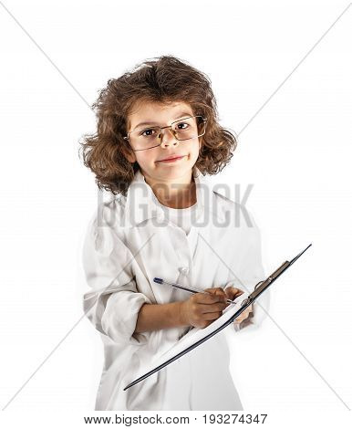 Young curly-haired boy writes in a notebook. White background.
