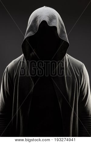 silhouette of mysterious man in the hood. mysterious hooded man silhouette hidden face. scary looking silhouette of hooded man. man in the hood silhouette over dark grey background