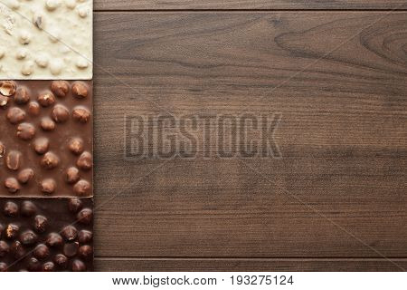 black, milk and white chocolate bars. different chocolate on brown table. chocolate bars with whole hazelnuts. chocolate bars on wooden background. different chocolate bars with whole hazelnuts with copy space