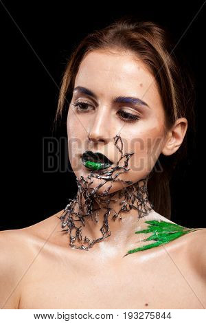 Beautiful Woman with decorative creative fashion make up on black background in studio photo. Cosmetics and extravagant makeup