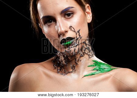 Gorgeous Woman with decorative creative fashion make up on black background in studio photo. Cosmetics and extravagant makeup