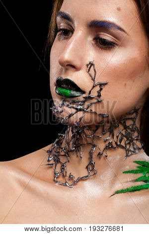 Beauty portrait of woman with creative makeup on black background in studio photo. Cosmetics and extravagant makeup
