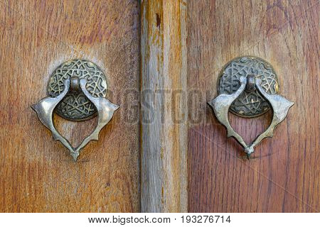 Closeup of two antique copper ornate door knockers over an aged wooden ornate door Fatih Mosque Istanbul Turkey