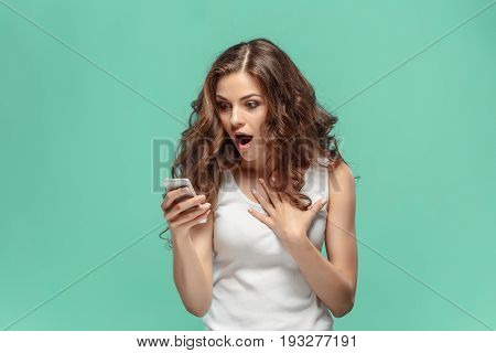 Shocked woman looking at mobile phone on green studio background