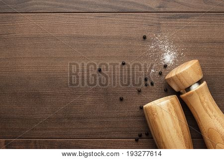 wooden pepper mill and salt shaker on the brown table. pepper mill and salt shaker overturned. stylish pepper mill and salt shaker on the wooden background. wooden pepper mill and salt shaker with copy space