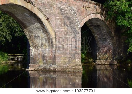 Image of two arches of a stone built bridge spanning a river