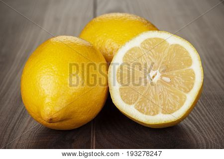 fresh lemons on the brown table. ripe lemons on the wooden background. fresh lemon sliced in half. juicy lemons for healthy diet