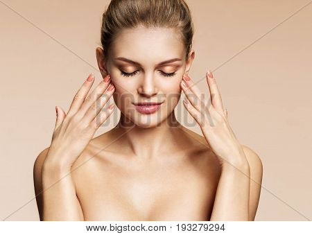 Attractive girl with beautiful make up touching her face. Photo blonde girl of on beige background. Beauty & Skin care concept