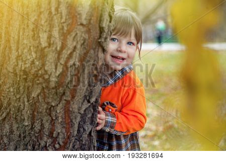 Little girl in orang checkered dress  is playing hide and seek in the park.