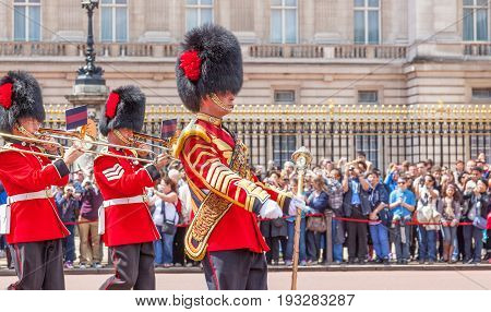 LONDON UNITED KINGDOM - JULY 11 2012: Led by a smart Drum Major, the band of the Coldstream Guards marches in front of Buckingham Palace during the Changing of the Guard ceremony.