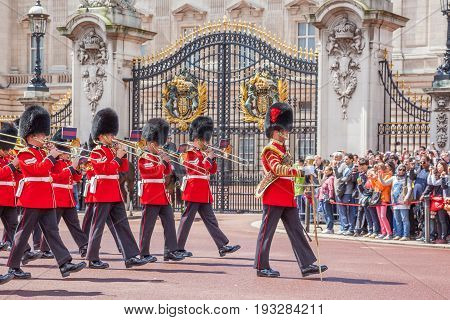 LONDON UNITED KINGDOM - JULY 11 2012: The band of the Grenadier Guards, led by a Drum Major of the Coldstream Guards, marches past the front of Buckingham Palace during the Changing of the Guard ceremony.