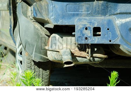 Rusty exhaust pipe on damaged car without rear bumper.