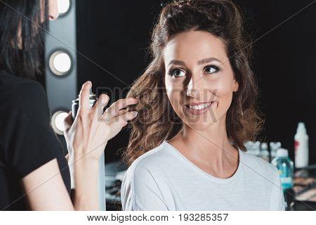 Hair Dresser Using Hair Spray To Finish Hairstyle In Beauty Salon