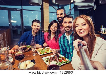 leisure, technology, friendship, people and holidays concept - happy friends having dinner and taking picture by selfie stick at restaurant