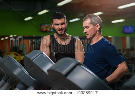 Senior man working with personal trainer in gym. Male adult exercising on treadmill with assistance of fitness coach. Healthy lifestyle, fitness and sports concept.