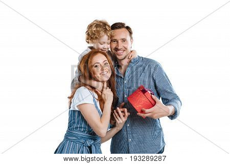 Cheerful Man With Adorable Little Son Presenting Gift Box To Young Woman And Smiling At Camera