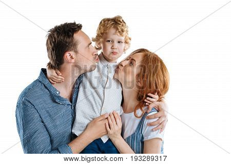 Happy Parents Able To Kiss Adorable Little Son Isolated On White