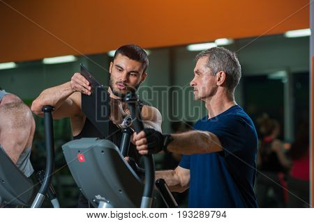 Senior man working with personal trainer in gym. Male adult exercising on elliptical machine while fitness coach showing training plan on clipboard. Healthy lifestyle, fitness and sports concept.