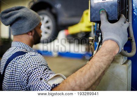 Car repairman pressing button to descend machine