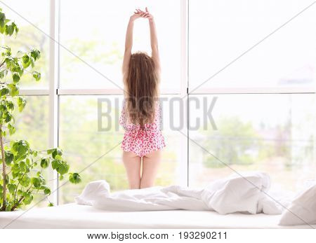 Morning of beautiful young woman standing near window at home