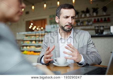 Professional traders explaining online data to co-worker in cafe