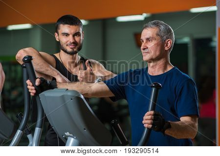 Senior man working with personal trainer in gym. Male adult exercising on elliptical machine with assistance of fitness coach. Healthy lifestyle, fitness and sports concept.