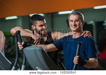 Happy smiling senior man working with personal trainer in gym. Male adult exercising on elliptical machine with assistance of fitness coach. Healthy lifestyle, fitness and sports concept.