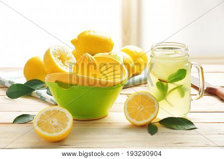 Squeezer and lemon juice in mason jar on wooden table