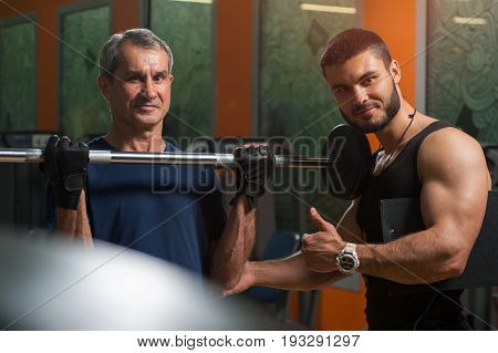 Senior caucasian man doing biceps exercise with barbell with personal trainer. Male adult exercising with assistance of fitness instructor. Healthy lifestyle, fitness and sports concept.