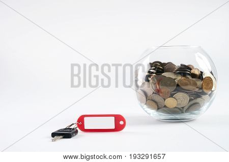 Piggy box with money and key with tag isolated on white background copy space close-up. Concept for real estate or renting home. Concept of saving money for a house.Business Finance and Money concept Save money for prepare in the future.