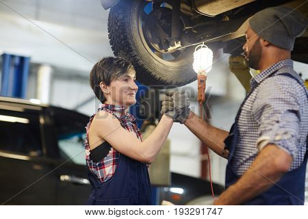 Two car service workers shaking hands