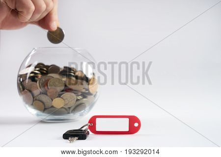 Hand put money on glass piggy bank filled with coins. Key with tag of new house isolated on white background with copy space concept in finance save buying and selling house