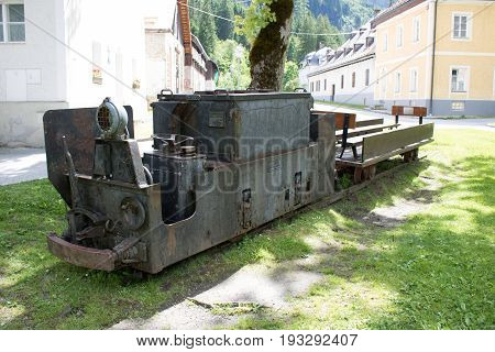Bad Gastein Austria - JUNE 09 2017: Old mining truck in front of the Health resort Heilstollen a former mining tunnel. Near Bad Gastein Austria Europe. Hammer and pick as symbols of mining.