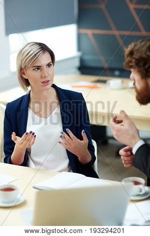 Woman explaining her idea to co-worker at meeting